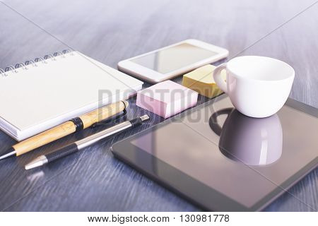 Closeup of tablet coffee cup pens stickers notepads and smart phone on dark wooden desktop