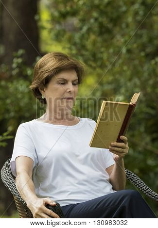Portrait of Senior Woman Reading a Book in a Garden