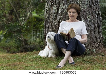 Pretty senior woman reading a book under the tree with a dog sitting beside her