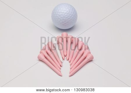 Wooden golf tees and white golf ball on the white background