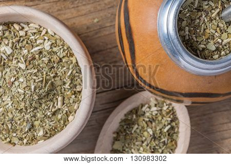 cup of dry yerba mate leaves on wooden table