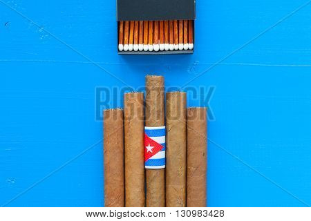 Detail of luxury Cuban cigars on the blue desk