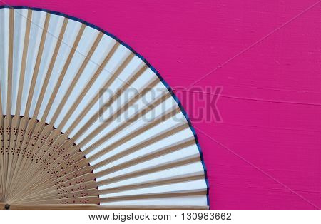 Typical Japanese hand fan made on the wooden pink table