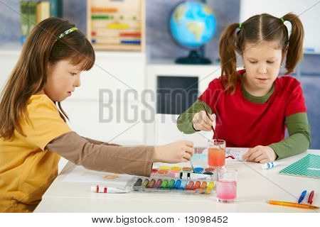 Elementary age children sitting around desk enjoying painting with colors in art class at primary school classroom.