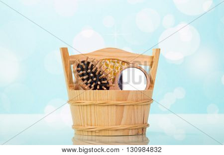 Wooden bucket with hairbrush and mirror on a blue abstract background.