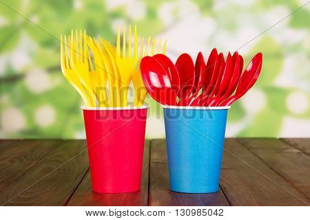 Bright plastic disposable tableware on abstract green background.