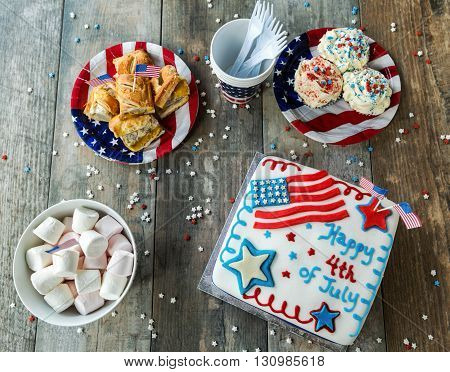 4th of July cake with cupcakes, marshmallows and hot dogs on wooden table, seen from above
