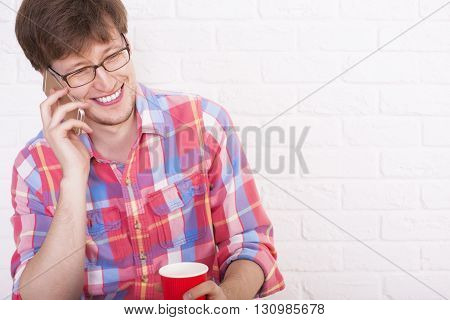 Young man with coffee cup in hand using cellphone on white brick wall background