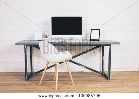 Front view of modern white chair and designer desk with blank computer screen and picture frames on white brick background. Mock up