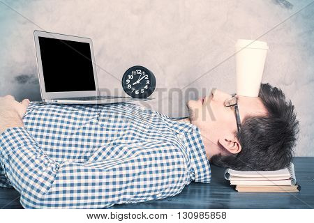 Young caucasian guy with blank laptop screen sleeping on office desktop with coffee cup on forehead. Mock up