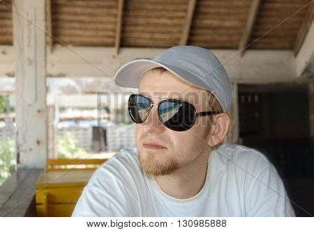 Young Man In Sunglasses And Cap Sitting