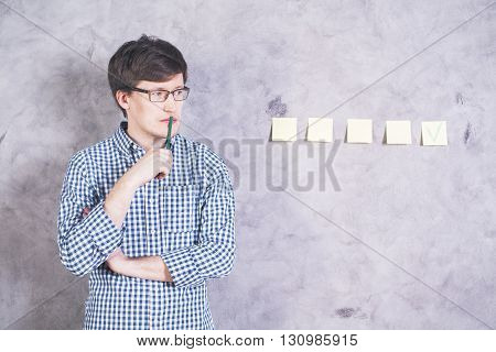 Thinking caucasian guy with green pencil at mouth looking at concrete wall with green check mark on stickers