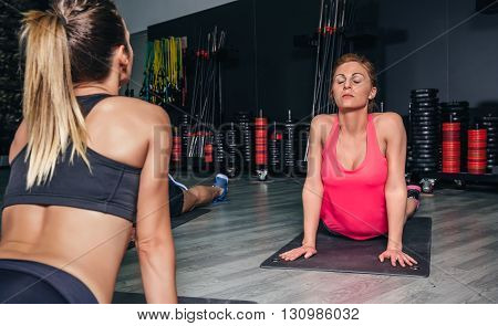 Portrait of redhead woman stretching her back after training on sports center
