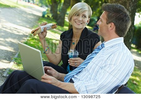 Young businesspeople sitting on bench in park having luch and looking at laptop computer.