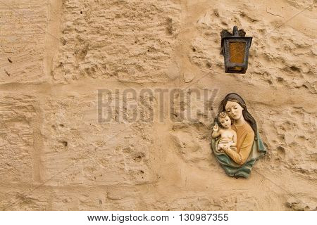 Small statue of Virgin Mary and a Child under a lantern on a texture wall of a house at the mediterranean island Malta.