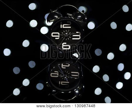 Bokeh spots of lights with alarm clock on a reflective surface
