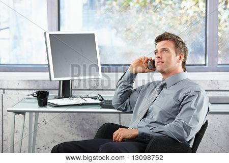 Mid-adult businessman sitting in office chair looking up speaking on mobile phone.