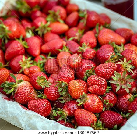 Top view of tasty strawberries collected on a box