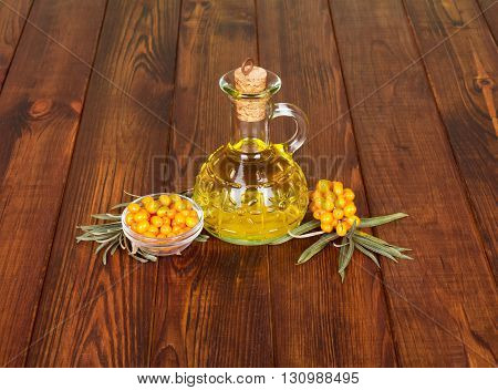 Sea buckthorn oil and berries on a background of dark wood.