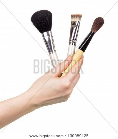 Cosmetic brush in a female hand isolated on white background.