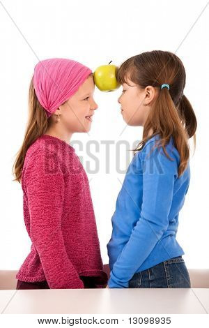 Laughing small girls facing each other, holding two apples together with forehead.
