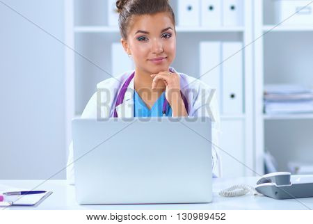 Female doctor sitting on the desk and working a laptop in hospital
