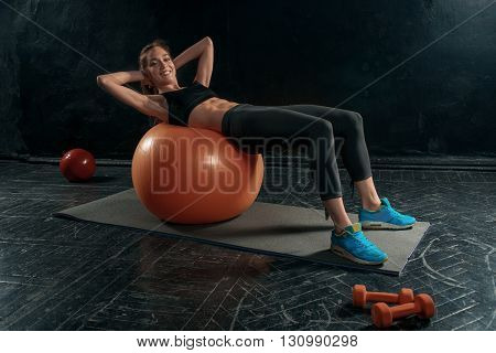 Beautiful young slim woman doing some gymnastics at the gym with fitball