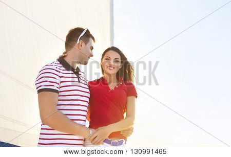 Young smiling couple on a sailing boat at summer sunset