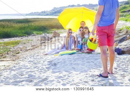 Friends sitting on the sand at the beach at the summer picnic. One man holding green bucket with lemonade. Close up