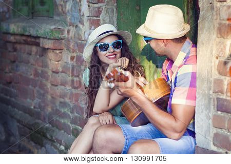 Romantic young couple playing Guitar outdoor. Love and travel concept