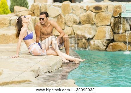 Young couple relaxing by the pool on a summer day