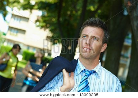 Portrait of casual businessman walking with suit droped over shoulder in park.