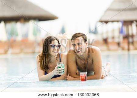 Young couple relaxing with drinks by the pool