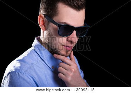 Young Handsome Man In Sunglasses Thinking About Something Over Black