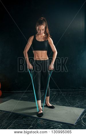 Beautiful young slim woman doing stretching exercises at the gym with a rubber band