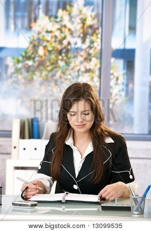 Young woman working at office table.