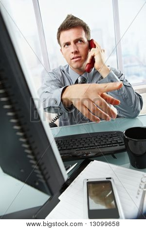 Serious businessman talking on landline phone gesturing out of picture sitting at office desk.