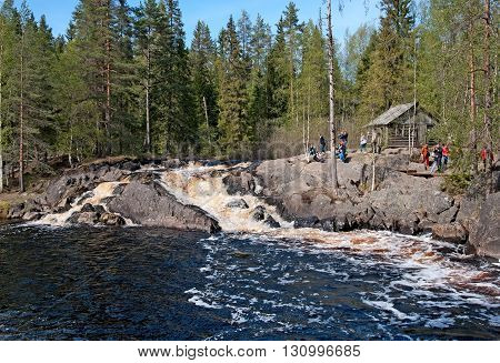 RUSKEALA, KARELIA, RUSSIA - MAY 14, 2016: Excursion group near Ahvenkoski Waterfall on Tohmajoki River. It is one of the four plain waterfalls (Ruskeala Waterfalls) in Sortavala District of Karelia