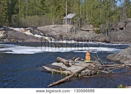 RUSKEALA, KARELIA, RUSSIA - MAY 14, 2016: Wooden beaver near Ahvenkoski Waterfall on Tohmajoki River. It is one of the four plain waterfalls (Ruskeala Waterfalls) in Sortavala District of Karelia