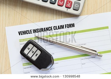 Vehicle insurance claim form concept with car key and calculator lay down on wooden desk.