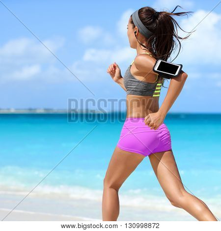 Fit woman running working out cardio exercise on summer tropical beach. Unrecognizable athlete runner jogging intense wearing phone armband holder for music motivation listening on smartphone app.