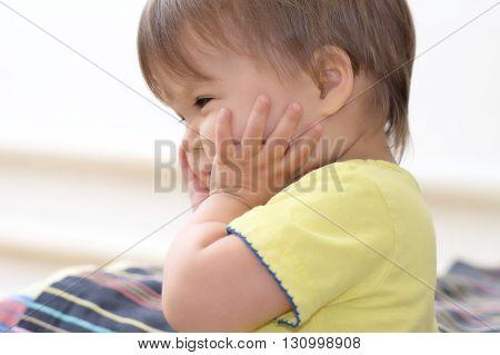 Baby Caucasian girl holding her sweet cheeks