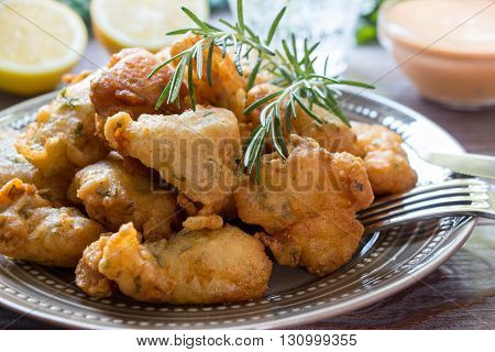In the foreground shrimps in crispy dough on a plate with rosemary, cutlery, in the background glass of water, lemon, herbs, bowl with sauce. Shrimps in pastry for lunch. Horizontal. Close.