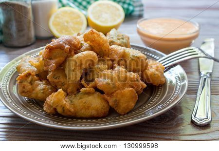 In the foreground shrimps in crispy dough on a plate, in the background cutlery, salt, pepper, lemon and bowl with the sauce. Shrimps in pastry for lunch. Horizontal. Daylight. Close-up.