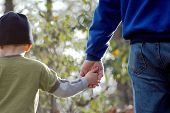 image of holding hands  - a grandfather and grandson hold hands and talk while hiking - JPG