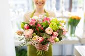 people, business, sale and floristry concept - close up of florist woman holding bunch at flower sho poster