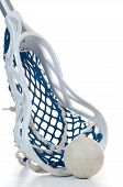 image of lax  - A sliver lacrosse stick with a white head and blue netting along with a gray ball - JPG