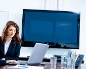 Young businesswoman sitting by meeting table at office in front of a huge blank plasma TV screen and