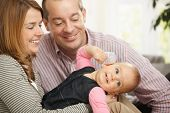 pic of nuclear family  - Smiling baby girl held by happy mother - JPG