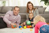 image of nuclear family  - Smiling family of four playing with balls on living room floor - JPG